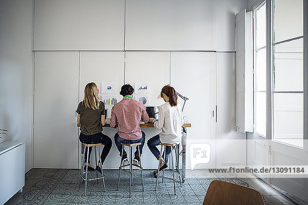 Rear view of business people sitting on stools while working in creative office