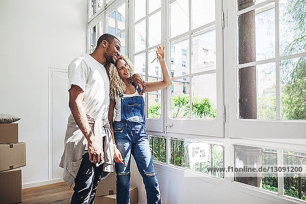 Smiling couple looking at keys while standing by window at home