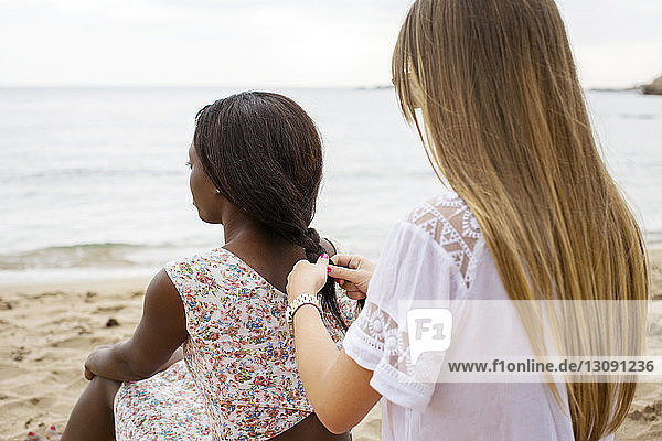 Rear view of woman braiding friend's hair while sitting on shore at beach