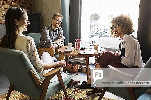 Glückliche Geschäftsleute sitzen am Fenster in der Hotellobby