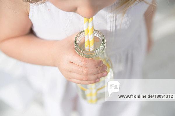 Hochwinkel-Mittelteil eines Mädchens  das mit Strohhalmen aus der Flasche Wasser trinkt Hochwinkel-Mittelteil eines Mädchens, das mit Strohhalmen aus der Flasche Wasser trinkt