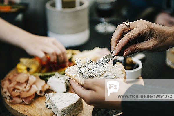Woman applying cheese on bread while sitting at table in backyard