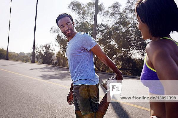 Mann sieht Frau an  während er sich auf der Straße streckt