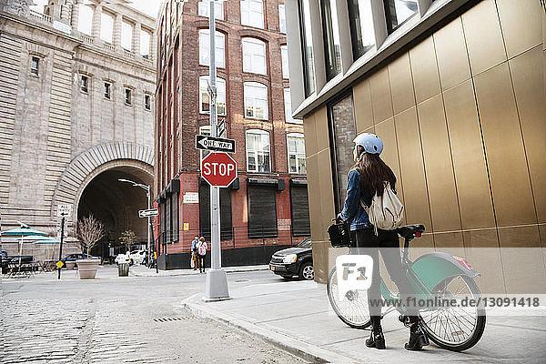 Frau geht mit dem Fahrrad auf dem Bürgersteig an einem Gebäude in der Stadt vorbei