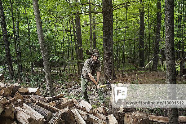 Mann mit Hut beim Brennholzschlagen mit dem Hammer im Wald