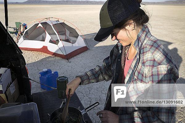 Hochwinkelaufnahme einer Frau  die in der Alvord-Wüste auf einem Fahrzeug Essen kocht