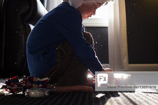 Junge in warme Kleidung gehüllt anwesend  während er zu Hause auf dem Teppich kauert