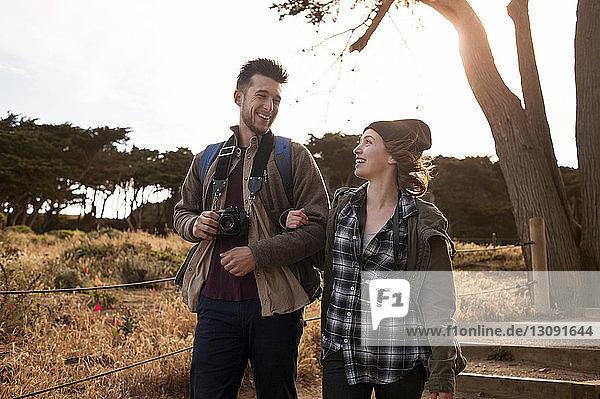 Glückliches wanderndes Ehepaar auf dem Feld