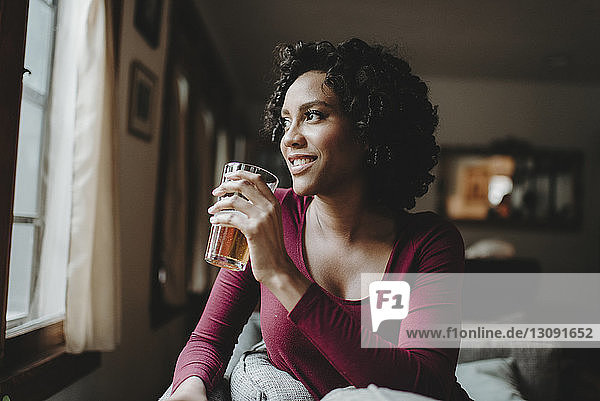 Thoughtful woman having drink while looking through window at home