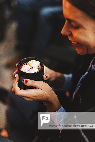 Smiling woman with marshmallow drink in backyard
