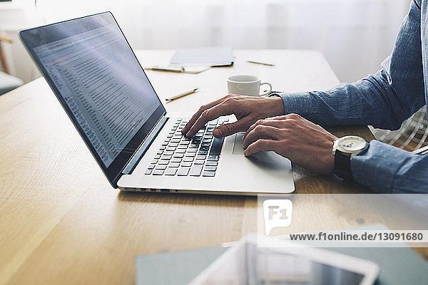 Mittelteil eines Geschäftsmannes  der einen Laptop am Schreibtisch im Büro benutzt