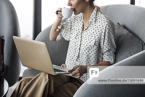 Frau trinkt Kaffee  während sie im Restaurant am Laptop arbeitet