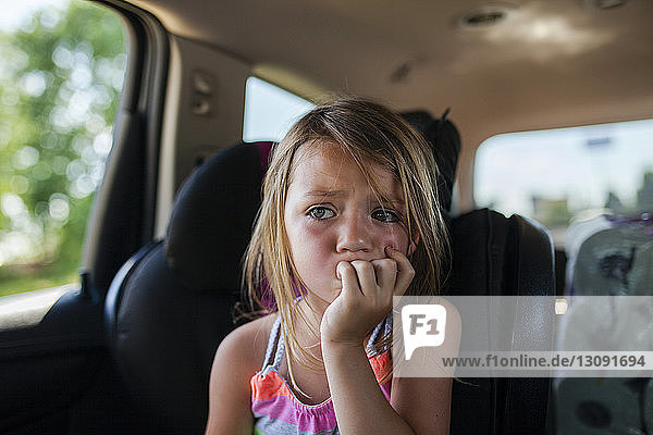 Upset girl looking away while sitting in car
