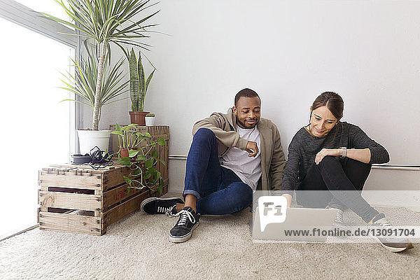 Lächelnde Geschäftsleute  die einen Laptop benutzen  während sie im Kreativbüro am Boden sitzen