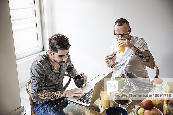 Gay men using laptop and reading newspaper while having breakfast at home