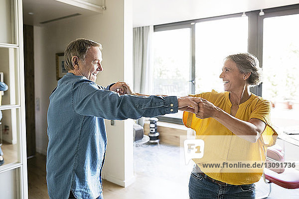 Cheerful senior couple dancing at home