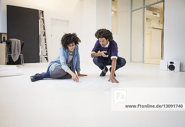 Young business colleagues discussing over chart while sitting on floor in creative office