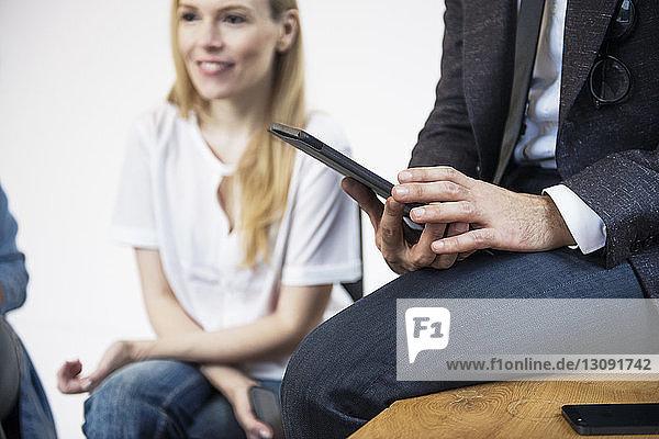 Mittelteil eines Geschäftsmannes  der einen Tablet-Computer benutzt  während er von einem Kollegen im Büro sitzt