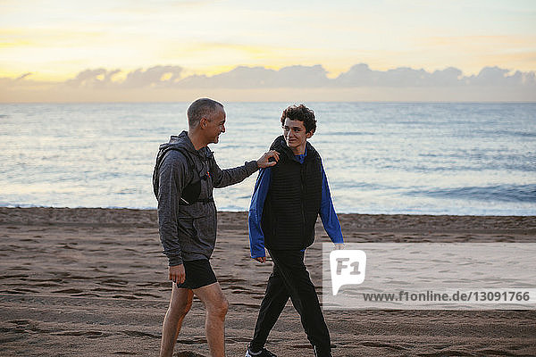 Happy father and son walking at beach against sky