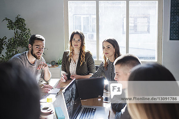 Students looking at friend while discussing at table in classroom
