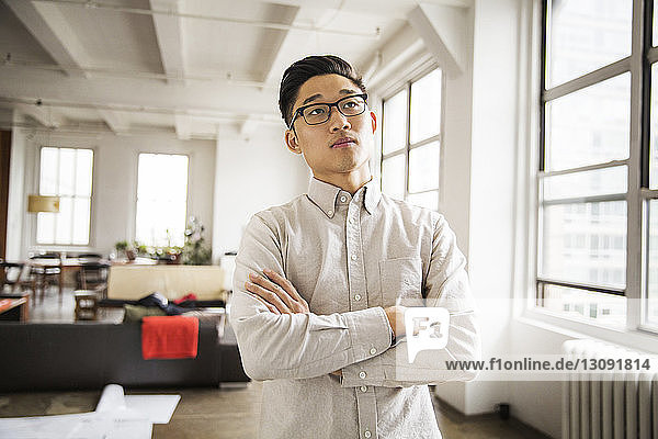 Confident businessman standing with arms crossed in brightly lit creative office