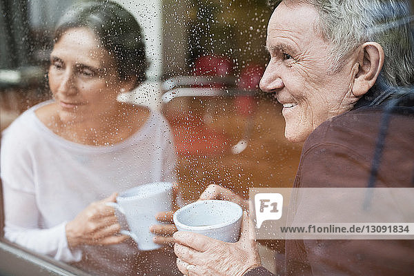 Happy senior couple looking through window at home
