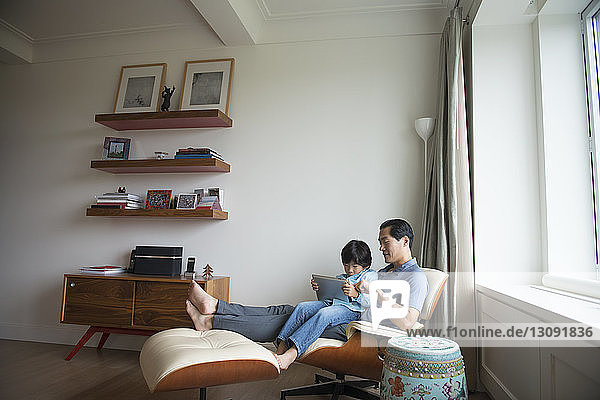 Father and son using tablet while sitting against wall at home