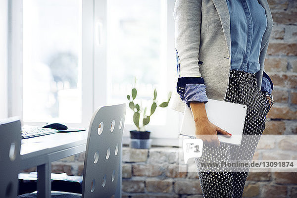 Midsection of businesswoman holding tablet computer in office