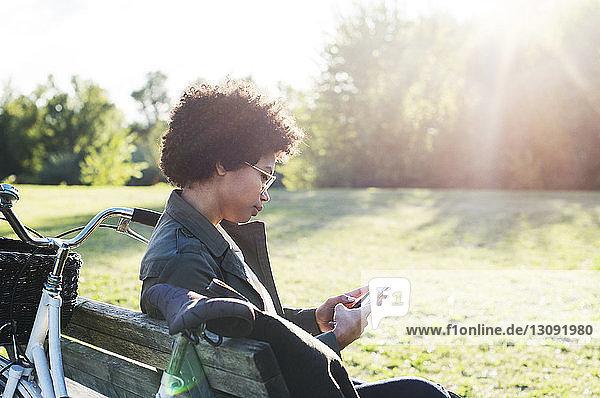 Frau telefoniert an sonnigen Tagen auf Parkbank sitzend