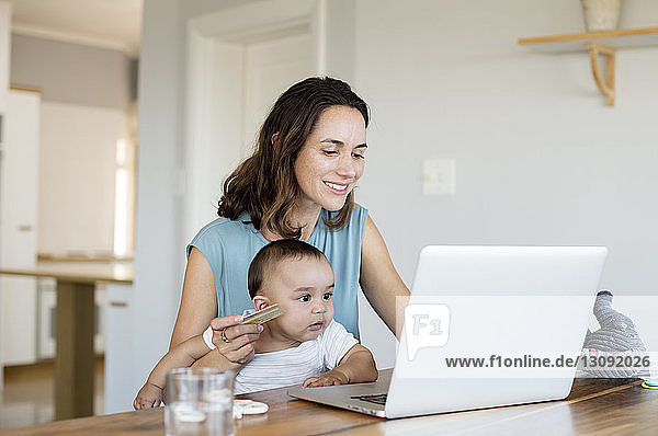 Woman with baby boy online shopping while using laptop computer at home