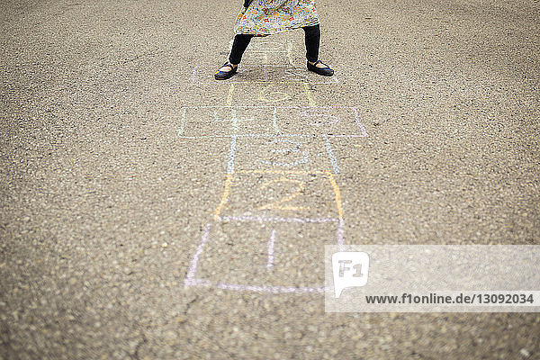 Low section of girl playing hopscotch on street