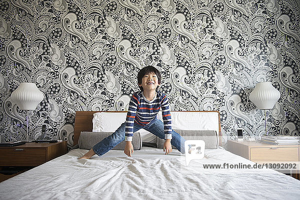 Happy boy standing with legs apart on bed