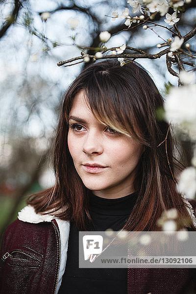 Nahaufnahme einer nachdenklichen jungen Frau  die am Park an Ästen wegschaut