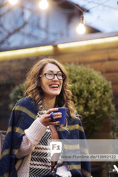 Fröhliche Frau schaut weg  während sie im Hinterhof eine Tasse hält