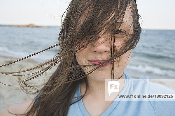 Close-up portrait of girl standing at beach against sky