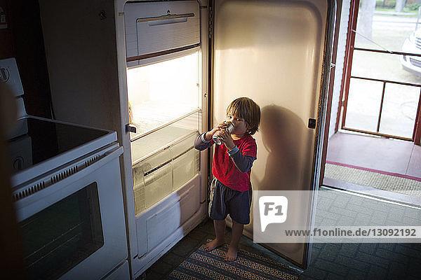 Boy drinking canned drink from fridge