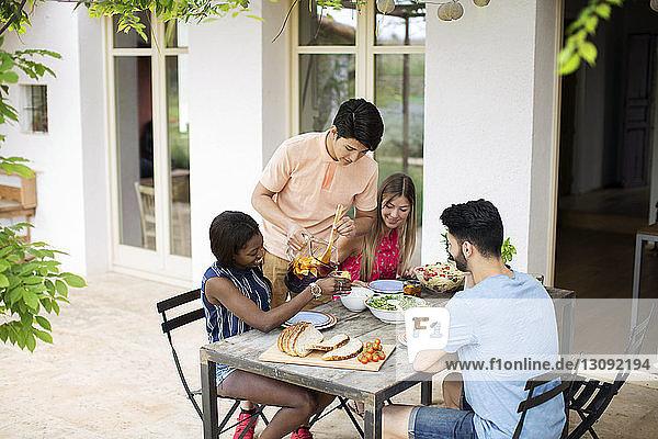 Mann serviert Freunden Eistee an einem Tisch im Freien