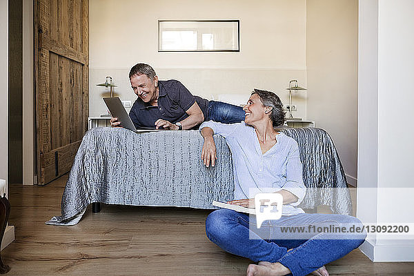 Happy woman looking at senior man using laptop in bedroom