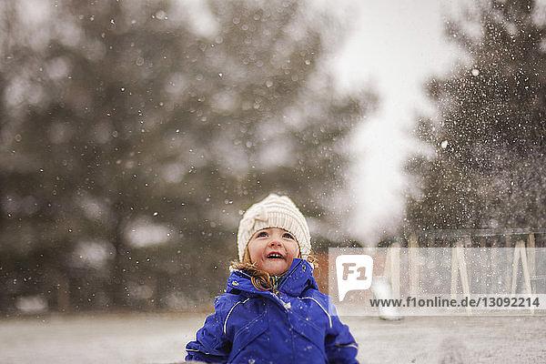 Happy girl enjoying snowfall