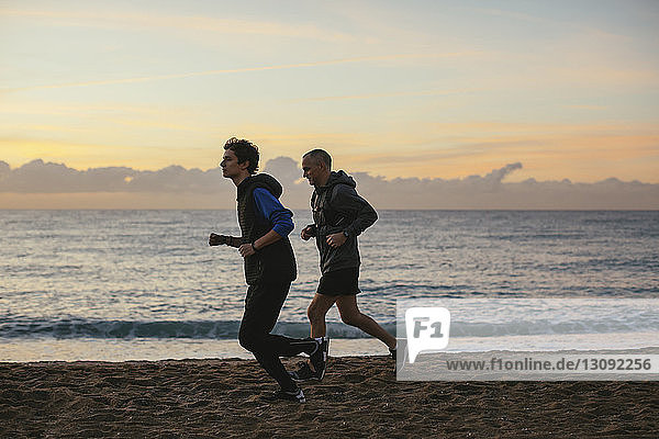 Side view of father and son jogging at beach against sky during sunset