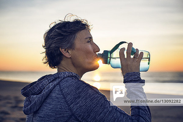Close-up of woman drinking water at beach against sky