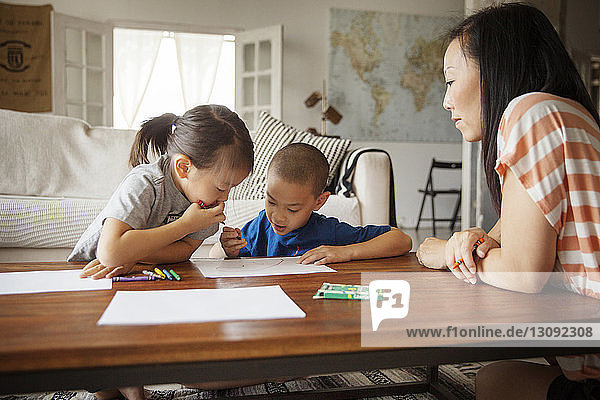 Mother looking at children drawing on table in living room
