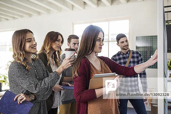 Schüler schauen auf die Tafel  während sie im Klassenzimmer stehen