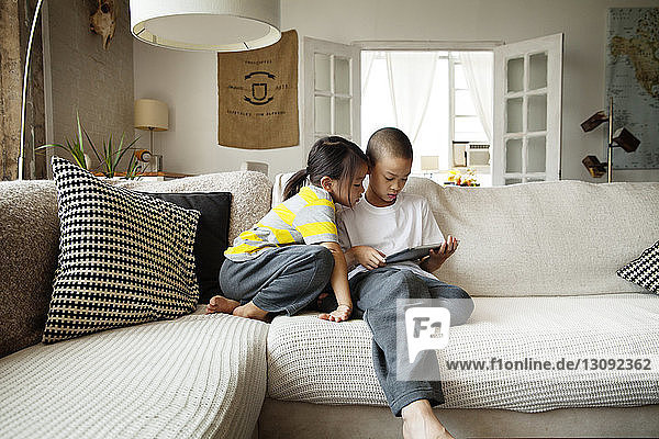Sister looking at brother using tablet computer while sitting on sofa in living room