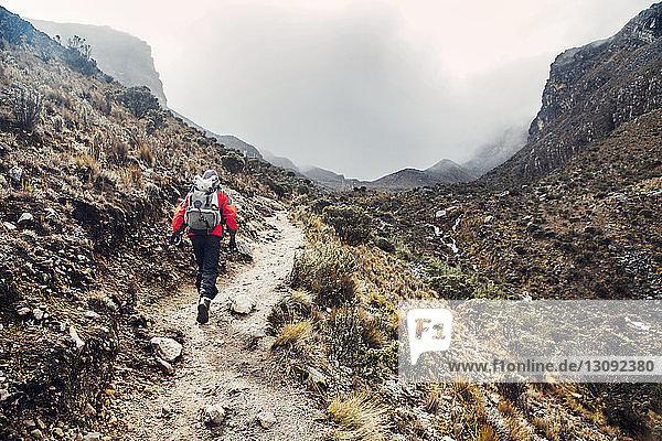 Hiker walking along mountain trail