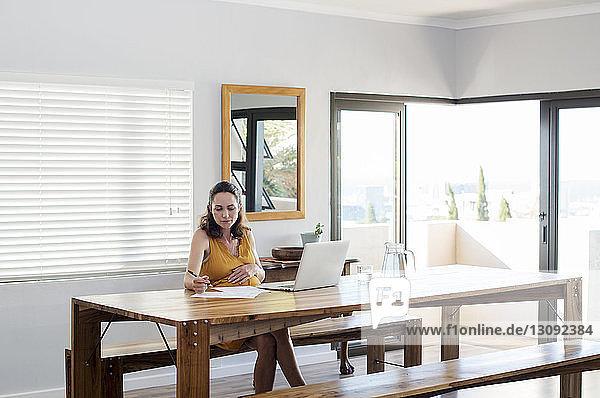 Schwangere Frau schreibt auf Papier  während sie am Tisch einen Laptop benutzt