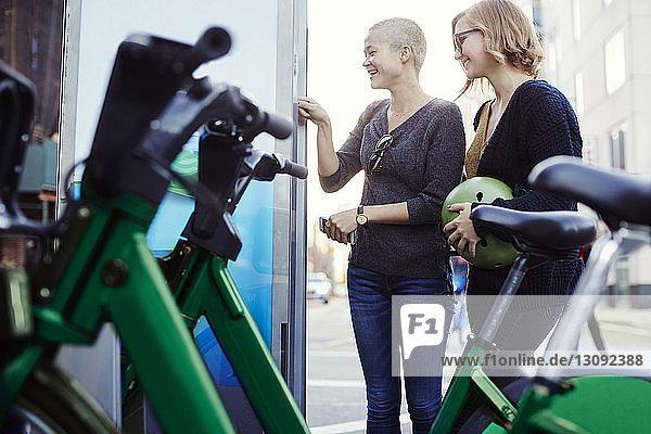Glückliche Freunde stehen am Fahrradparkplatz in der Stadt