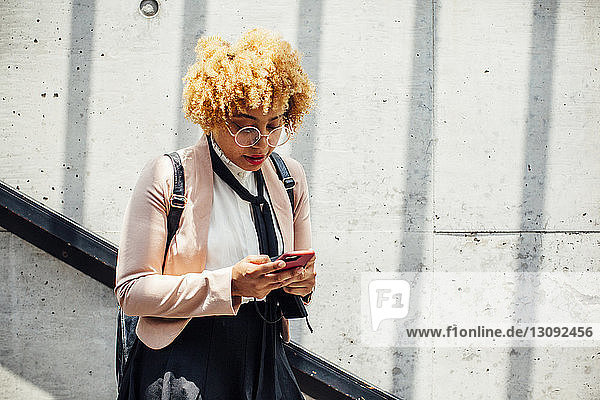 Woman using smart phone while standing by wall