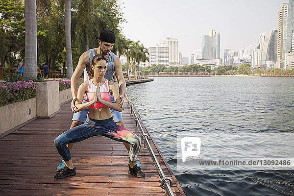 Man assisting woman in exercising on wooden walkway by river