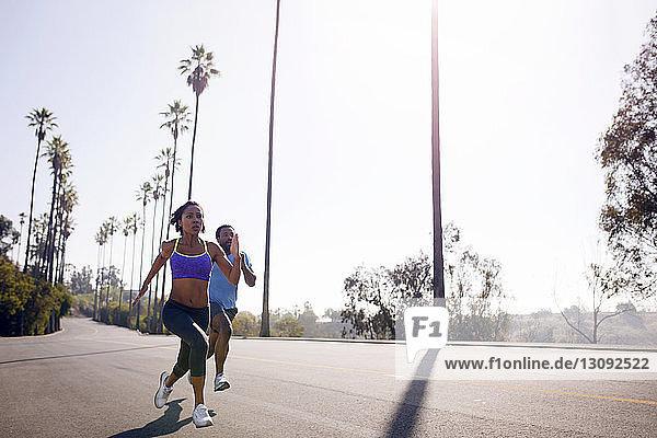 Entschlossenes Paar joggt bei Sonnenschein auf der Straße
